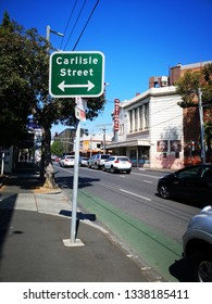 Melbourne, Australia: March 14, 2019: Street sign for Carlisle Street in St Kilda. A typical Melbourne suburb with traffic old style buildings and a busy residential environment.