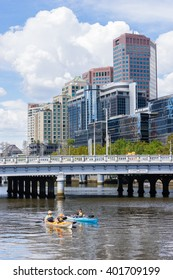 Melbourne, Australia - March 17, 2016: View of tourists on kayak tour along the Yarra River with cityscape of Melbourne as background. Kayaking is a new and fun way to see Melbourne.