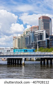 Melbourne, Australia - March 17, 2016: View of a tram crossing the bridge and cityscape of Southbank in Melbourne with hotels and modern office buildings during daytime.