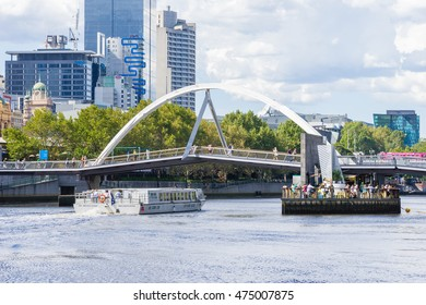 Melbourne, Australia - March 17, 2016: View of floating bar under the Yarra Pedestrian Footbridge and cruise boat with skyscrapers behind it in Melbourne during daytime.
