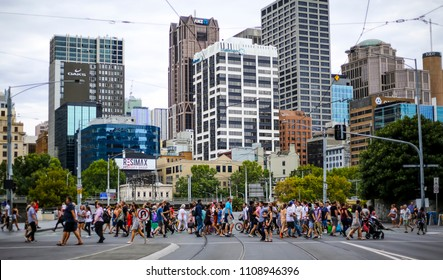 MELBOURNE, AUSTRALIA - MARCH 19, 2018 : People walking across a busy crosswalk in downtown Melbourne.