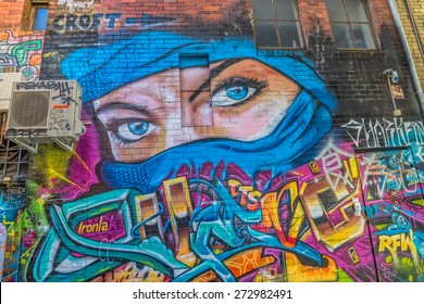 MELBOURNE, AUSTRALIA - MARCH 21, 2015: Colorful graffiti in back alley of downtown, depicts an blue eyes of a woman in a blue scarf.