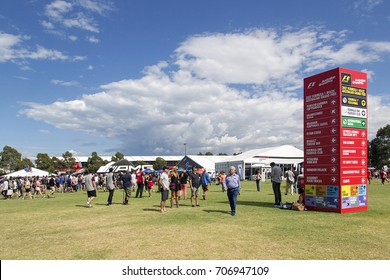 Melbourne, Australia: March 25, 2017: People walk around the event and exhibits at Melbourne's Formula One event in Albert Park. A large sign gives information and location to the grandstands