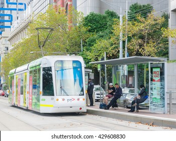 Melbourne, Australia - May 1, 2016: View of passengers in a tram station waiting for a E-Class tram in Melbourne. This three section articulated low-floor tram was introduced in Melbourne in 2013.