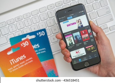Melbourne, Australia - May 10, 2016: Browsing the iTunes store and purchase movies with iTunes gift cards. iTunes store is an online store operated by Apple Inc, selling songs, apps, TV shows and