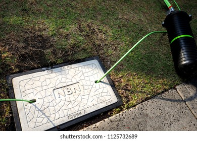 Melbourne, Australia - May 14, 2018: Pit with a concrete man hole cover displaying the NBN word mark with fibre optic cables in and out and a dome closure