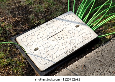 Melbourne, Australia - May 14, 2018: Pit with a concrete man hole cover displaying the NBN word mark with fibre optic cables in and out
