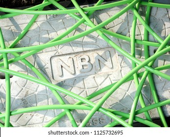 Melbourne, Australia - May 14, 2018: Green NBN fibre optic cable in a unstructured mess over a pit with a concrete man hole cover displaying the NBN word mark