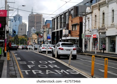 MELBOURNE, AUSTRALIA, May 23, 2014: A painted sign in Bridge Road, Richmond, warns drivers to stop for trams