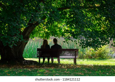 Melbourne, Australia - May 5, 2018: Couple enjoying the tranquility of a park bench in the Royal Botanic Gardens in Melbourne.