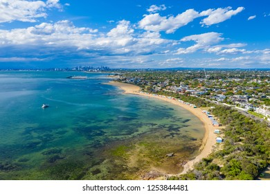 Melbourne, Australia - Nov 16, 2018: Aerial view of tourists visiting the Brighton Bathing Boxes, with Melbourne CBD in the background.