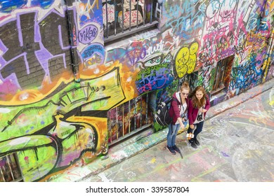 Melbourne, Australia - November 14, 2015: Two young, female tourists taking photos with smartphone selfie stick in Hosier Lane, Melbourne. Hosier Lane is one of the city's best street art locations.