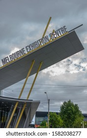 Melbourne, Australia - November 16, 2009: Closeup of Modern architectural concrete awning stuck on yellow poles with sign of Melbourne Exhibition Centre against gray cloudscape. Some green foliage.