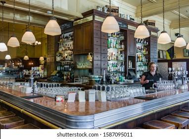 Melbourne, Australia - November 17, 2009: Belgian Beer Café Bluestone. The large bar with one female bar server behind. Plenty of glassware, lamps, taps and bottles of liquor on shelves.