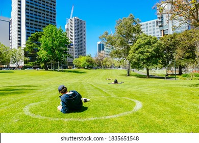 Melbourne, Australia - October 16th 2020: People enjoy the warm spring weather within social distance painted circles in Melbourne parks  during the Coronavirus pandemic and associated lockdown.