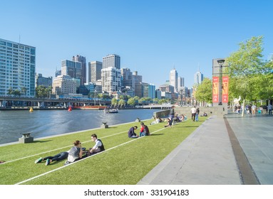 Melbourne, Australia - October 8, 2015: View of Melbourne's skyline and people sitting in lawn enjoying the sunshine in Southbank Promenade in Melbourne.