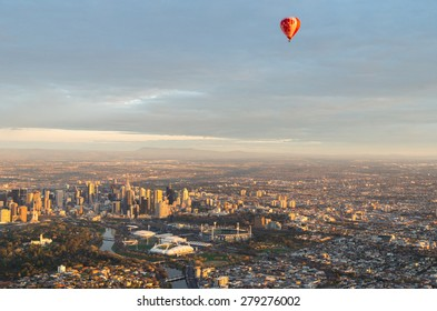 Melbourne, Australia - September 15, 2013: a hot air balloon floating above central Melbourne, the Melbourne Cricket Ground and tennis centre at sunrise.
