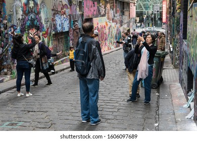 MELBOURNE, AUSTRALIA - SEPTEMBER 15, 2019: Tourists taking photos of the street art in the hidden laneways of Melbourne