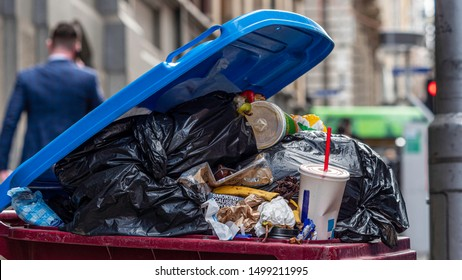 Melbourne, Australia - September 2019: Urban rubbish bin overflowing in a populous city. Food scraps, plastic waste, single use bags. Shows recycling problems or issues, waste management, etc.