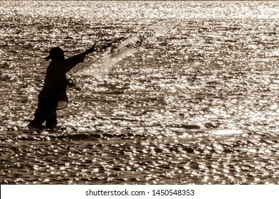 Melbourne Beach FL USA Oct 27, 2010. Silhouette of a cast net fisherman at sunset in Sebastian Inlet State Park
