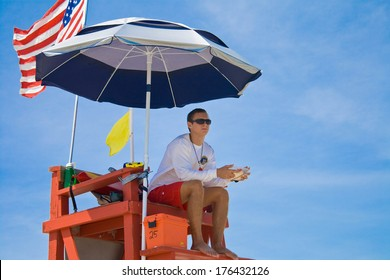 MELBOURNE BEACH, FLORIDA - SEPTEMBER 3, 2011: A lifeguard looks on vigilantly as tourists and locals alike enjoy the ocean.