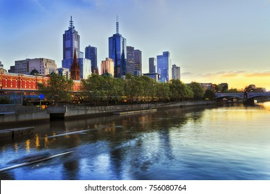 Melbourne city CBD on North side of Yarra river at Sunrise around Flinders train station and office high-rise towers.