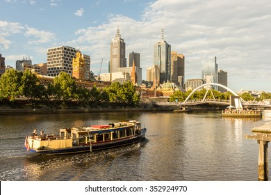 Melbourne City Skyline Cityscape from Southbank and Ferry Boat Cruise Yarra River full of Passenger tourist at sunset, Australia