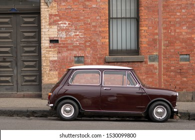 Melbourne Fitzroy, 27 July 2019 Classic Mini Cooper in burgundy red parking on the street at the front of vintage building.