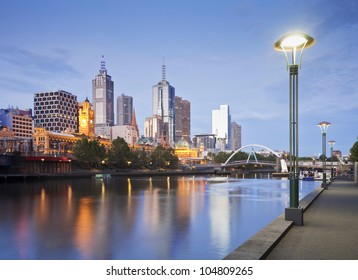 Melbourne skyline early on a summer evening, just as the lights start to come on, reflecting in the Yarra River.