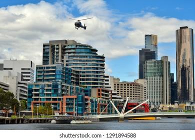 MELBOURNE, VIC, AUSTRALIA - NOVEMBER 03: Helicopter, buildings and Seafarers bridge over Yarra river in the capital of Victoria, on November 03, 2017 in Melbourne, Australia