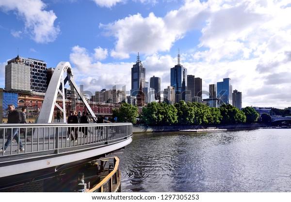 MELBOURNE, VIC, AUSTRALIA - NOVEMBER 03: Unidentified people on Evan Walker footbridge over Yarra river with floating cafe and bar named Ponyfish island, on November 03, 2017 in Melbourne, Australia
