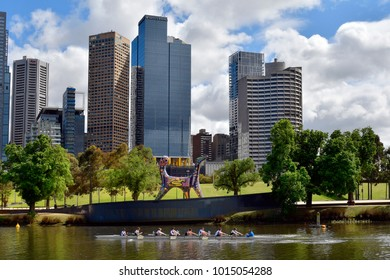 Melbourne, VIC, Australia - November 04, 2017: Unidentified people by training in rowing boat on Yarra river with sculpture named Angel and buildings