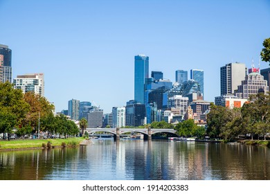 Melbourne, Victoria, Australia - 02.10.2021: The central business district of the city of Melbourne on the green river banks of the Yarra River on a sunny summer day under a bright blue sky.