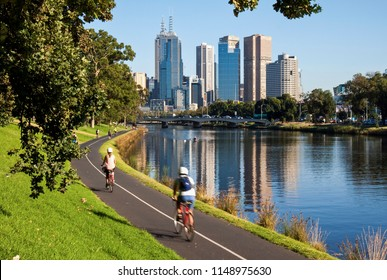 MELBOURNE, VICTORIA, AUSTRALIA - 18 FEBRUARY 2014: Cyclists riding along the Yarra River bike track towards the Melbourne City skyline in the distance on a warm summer's morning.