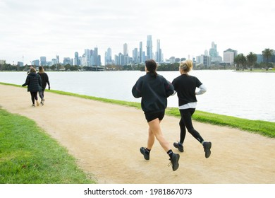 Melbourne, Victoria, Australia, 29 May 2021: two people running around Albert park lake against the Melbourne city skyline backdrop. People out exercising, runners and walkers on the track.