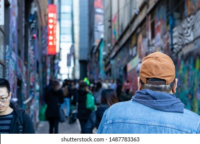 Melbourne, Victoria / Australia - Aug 22 2019: Person in a tan cap and denim jacket looking at the massive crowd that gathers at Hosier Lane