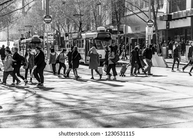 Melbourne, Victoria, Australia, August 25th 2018: Three Melbourne trams are stopped on Swanston Street and pedestrians are walking in the city.
