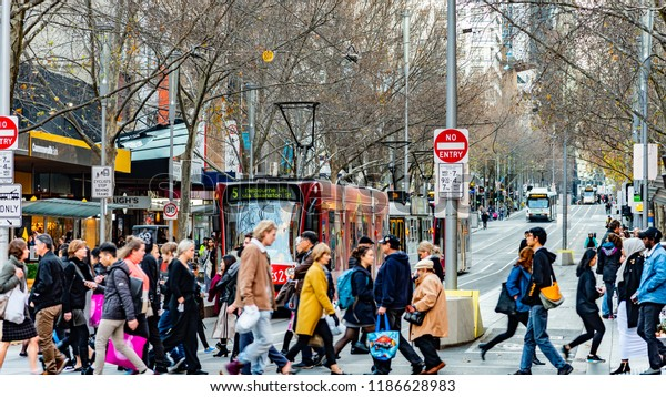 Melbourne, Victoria, Australia, July 14 2018: Five Public Transport Victoria trams are on Swanston Street while pedestrians cross the road at the intersection of Bourke Street.