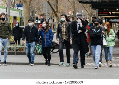 Melbourne, Victoria, Australia - July 23rd 2020: People don masks en masse on the first day of Victoria's mask rule. Crossing the street in the CBD, everyone in sight is now wearing a mask.