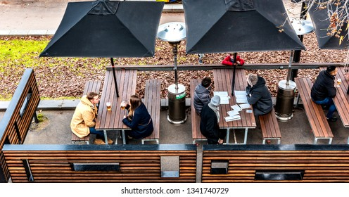 Melbourne, Victoria, Australia, June 24th 2018: People are sitting and drinking at an outdoor bar along side the yarra river during winter in Melbourne.