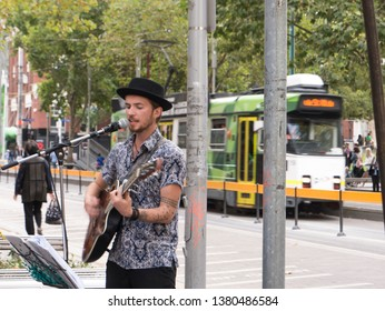 Melbourne, Victoria/ Australia- March 11th 2019: Man in Melbourne City busking with a guitar while a tram passes.