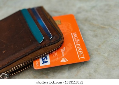 MELBOURNE, Victoria, Australia, March 8, 2019: ING Direct orange everyday debit card in brown wallet unzipped, visa paywave with chip on benchtop background