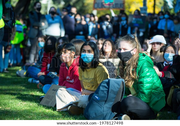 Melbourne, Victoria, Australia, May 21 2021: Concerned school children wearing face masks while sitting in the crowd attending a climate change strike. Students wearing face masks at protest.