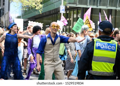 "Melbourne, Victoria, Australia: October-11-2019: Protestors of Extinction Rebellion engaging in peaceful ""Disco Disruption"" protest - Extinction rebellion flash mob in front of police"
