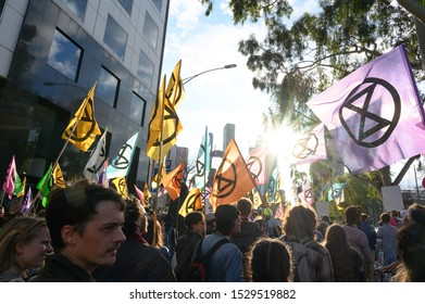 "Melbourne, Victoria, Australia: October-11-2019: Protestors of Extinction Rebellion engaging in peaceful ""Disco Disruption"" protest - Afternoon sun shines through Extinction Rebellion flags"