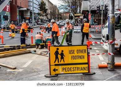 Melbourne, Victoria, Australia, September 8, 2018: Many road workers in orange vests are working on a busy inner city street.