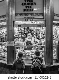 MELBOURNE, VICTORIA/AUSTRALIA July 14 2018: Two male children are looking in the window of a Queen Victoria Market stall while the shopkeeper looks on.