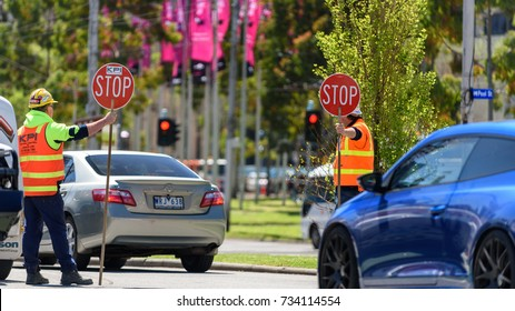MELBOURNE, VICTORIA/AUSTRALIA OCTOBER 14: Two traffic control workers are holding stop signs to stop the traffic at a roundabout on October 14 2017.