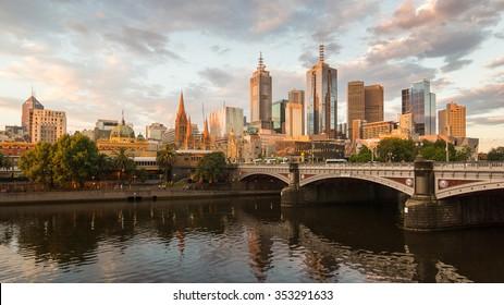 Melburne City, Yarra River, Princes Bridge with Reflection Cityscape Skyline background under dramatic Golden Sky Sunset, Australia