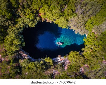 Melissani Cave Kefalonia viewed from above with tourists entering the cave by boat